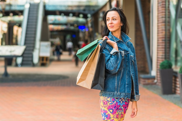 Lady with shopping bags in mall Free Photo
