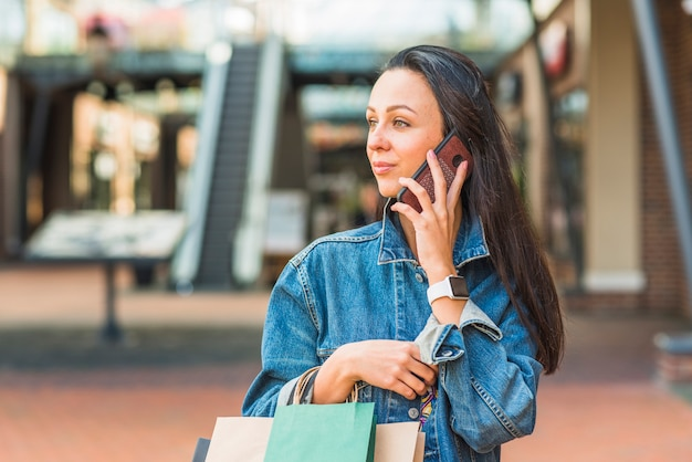 Lady with shopping bags and smartphone in mall Free Photo