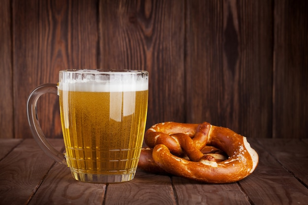 Lager beer glass and pretzel on wooden table Premium Photo