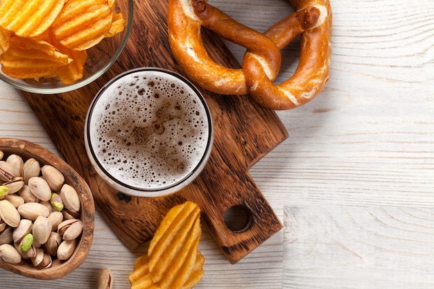 Lager beer mug and snacks on wooden table Premium Photo