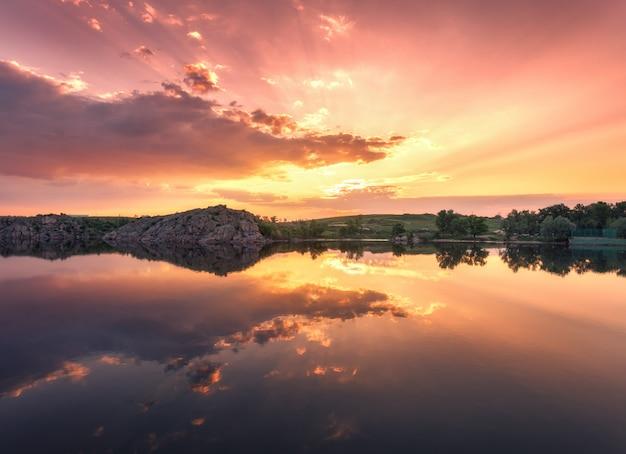Озеро против красочного неба с облаками на закате Premium Фотографии