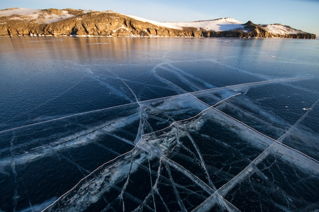 Lake baikal is covered with ice and snow, strong cold, thick clear blue ice. icicles hang from the rocks. lake baikal is a frosty winter day. amazing place, heritage, beauty of russia Premium Photo