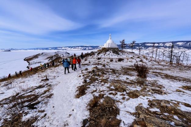 Озеро байкал, россия - 10 марта 2020 года: толпы туристов гуляют вокруг буддийской ступы на острове огой на озере байкал. огой - самый большой остров в проливе малое море на байкале. Premium Фотографии