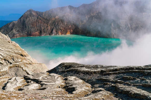Lake in the middle of a rocky landscape expelling smoke Free Photo