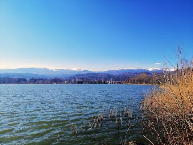 Озеро в окружении холмов и травы под солнечным светом и голубым небом в польше Бесплатные Фотографии