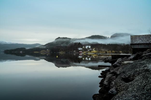 Lago circondato da colline coperte di nebbia con il verde che si riflette sull'acqua Foto Gratuite