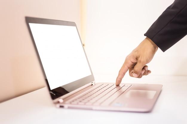 テーブルの上のlakptopを扱うビジネス男 Premium写真