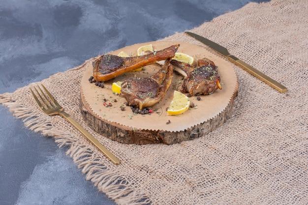 レモンスライスとテーブルクロスのカトラリーと木の板の子羊のチョップ。 無料写真