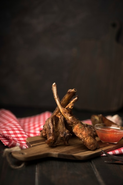 Lamb chops on wooden board with sauce Free Photo