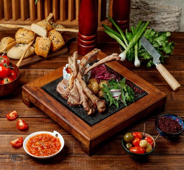 Lamb rib kebab served with fresh herbs, baby potato and tomato sauce Free Photo