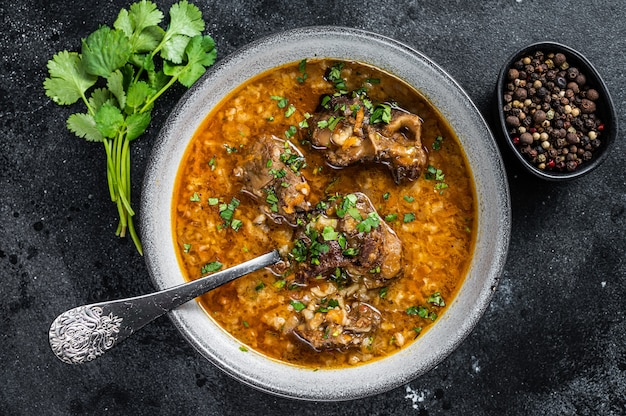Суп из баранины харчо с бараниной, рисом, помидорами и специями в миске. чернить Premium Фотографии