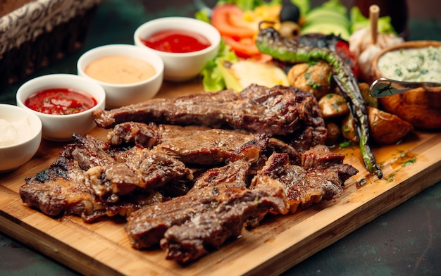 Lamb steak pieces with sauces, grilled pepper, fresh salad on wooden board Free Photo