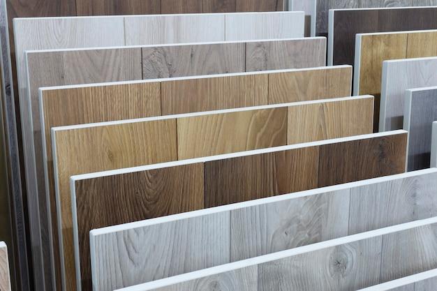 라미네이트 배경. 바닥 및 인테리어 디자인을위한 패턴 및 목재 질감이있는 라미네이트 또는 쪽모이 세공의 샘플. 목재 바닥 생산 프리미엄 사진