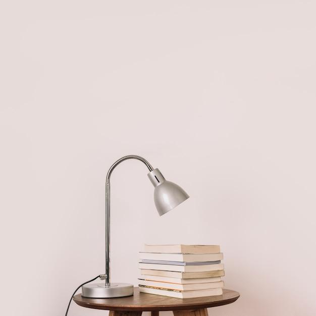 Lamp and books near white wall Free Photo