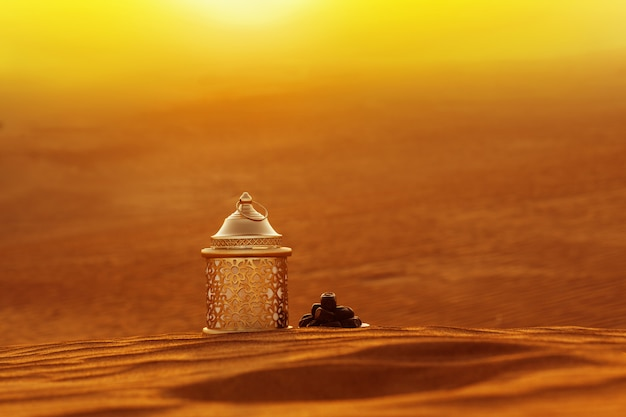 Lamp and dates stand on the sand overlooking a beautiful sunset Premium Photo