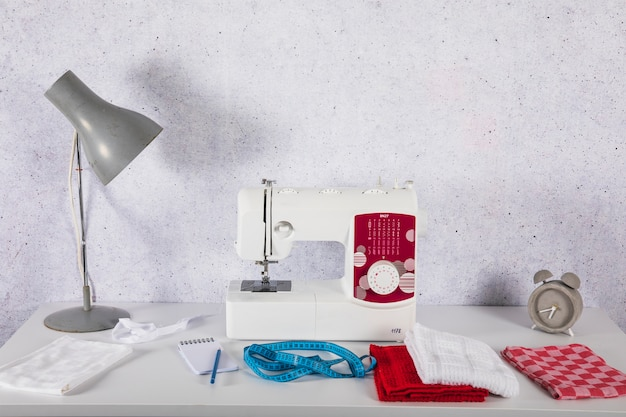Lamp near sewing machine on table Free Photo