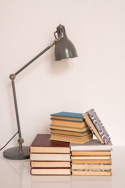 Lamp over stacks of books and manuals on table or workplace of student of college or school against white wall in studio Premium Photo
