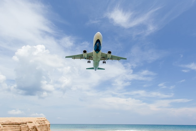 Landing aircraft above the beach at phuket airport. mai khao beach Premium Photo