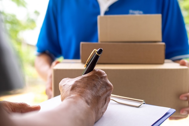 The landlord's hand is signing to receive the parcel sent by delivery man. Premium Photo