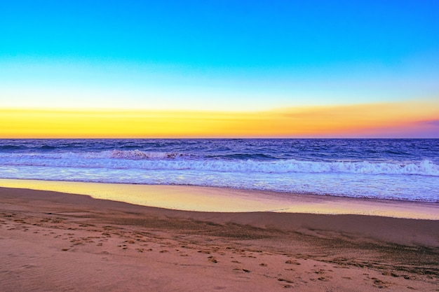 Landscape of a beach surrounded by sea waves during an orange sunset in the evening Free Photo