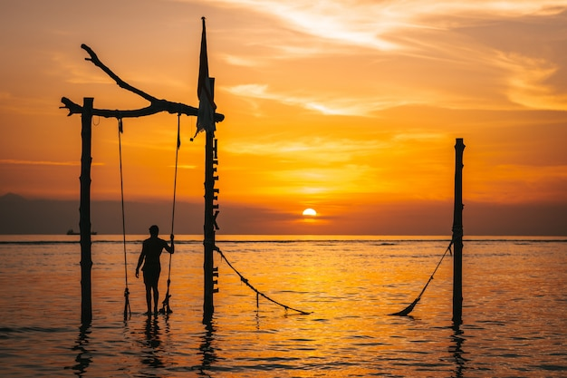 Landscape of the best sunset in gili island in famous swing in indonesia with, red sky Premium Photo