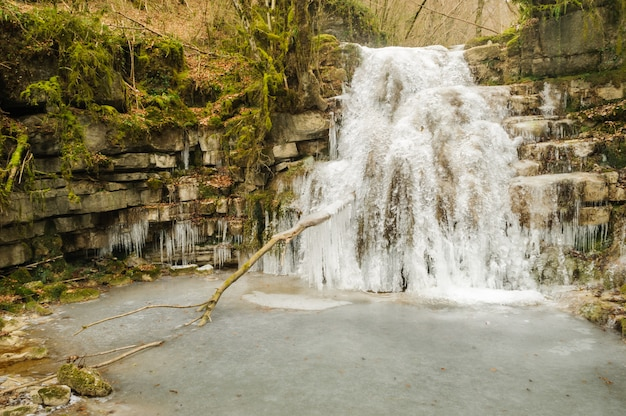 Landscape of frozen river and waterfall in a forest of spain Premium Photo