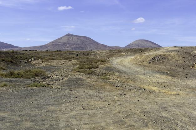 Paesaggio delle colline sotto un cielo blu nel parco nazionale di timanfaya in spagna Foto Gratuite