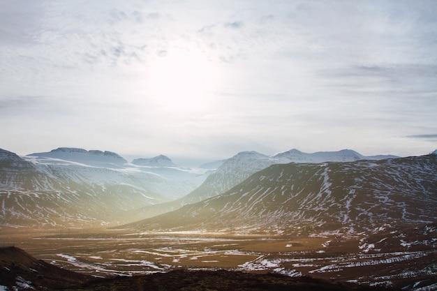 Paesaggio di colline coperte di erba e neve sotto un cielo nuvoloso e luce solare in islanda Foto Gratuite