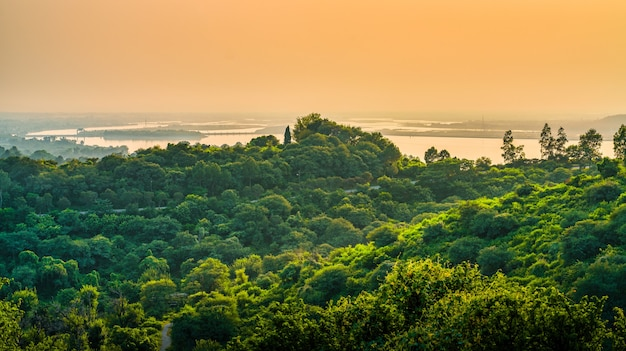 Landscape of hills covered in greenery surrounded by the sea under a cloudy sky during the sunset Free Photo