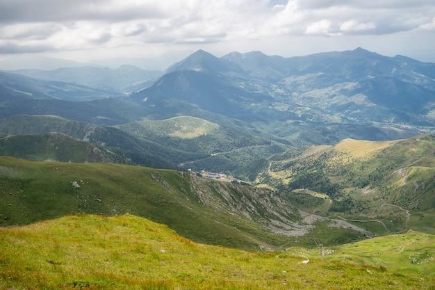 Paesaggio di colline ricoperte di vegetazione con montagne rocciose sotto un cielo nuvoloso Foto Gratuite