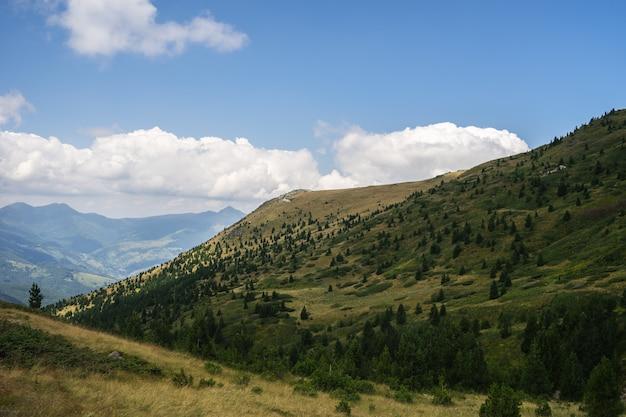 Paesaggio di colline ricoperte di vegetazione con montagne rocciose sotto un cielo nuvoloso sul Foto Gratuite