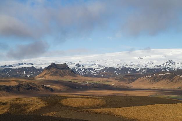 Paesaggio di colline coperte di neve sotto un cielo nuvoloso e luce solare in islanda Foto Gratuite