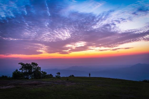 Landscape man on hill sky sunset clouds colorful sky blue purple Premium Photo