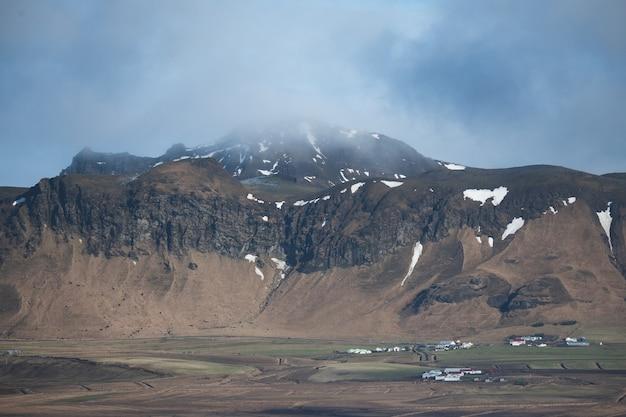 Paesaggio di montagne coperte di neve ed erba sotto un cielo nuvoloso in islanda Foto Gratuite