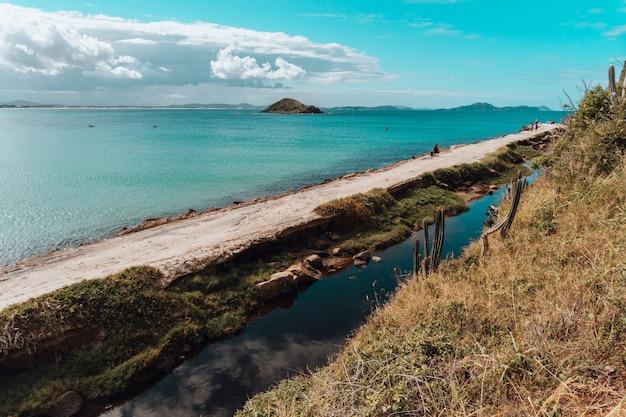 リオデジャネイロのビーチの砂の道と山の形成 無料写真