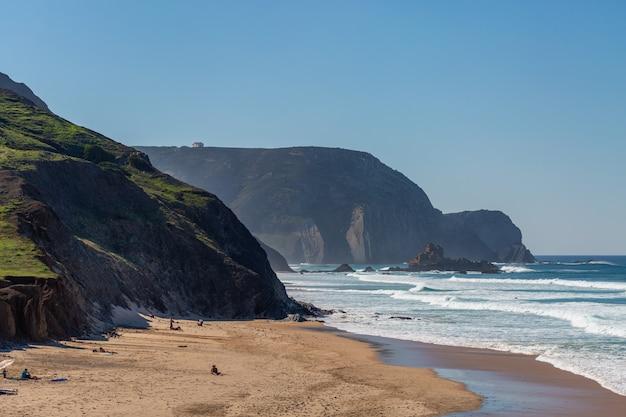Пейзаж пляжа, окруженного морем и горами, с людьми вокруг него в португалии, алгарве Бесплатные Фотографии