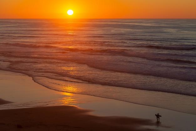 Ландшафт красивого захода солнца отражая на море от пляжа в португалии, алгарве Бесплатные Фотографии