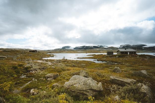 Пейзаж поля в окружении зелени и хижин под облачным небом в финсе, норвегия Бесплатные Фотографии