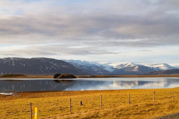 雪に覆われた丘に囲まれ、アイスランドの水に映る川の風景 無料写真