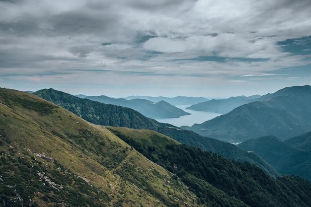 緑に覆われ、曇り空の下の川に囲まれた丘の風景 無料写真