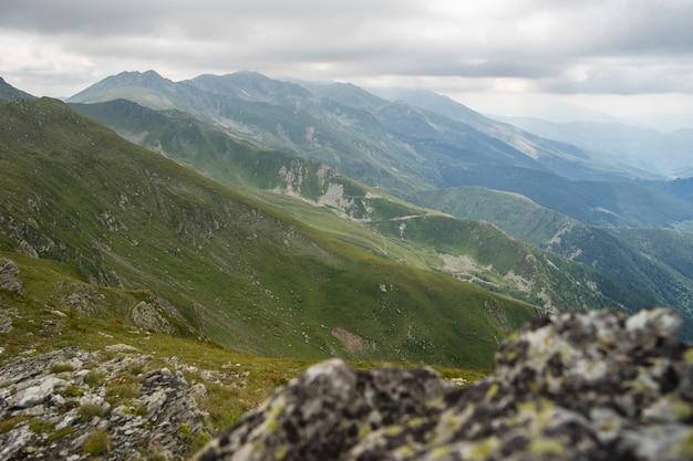 Пейзаж холмов, покрытых зеленью, со скалистыми горами под пасмурным небом на заднем плане Бесплатные Фотографии