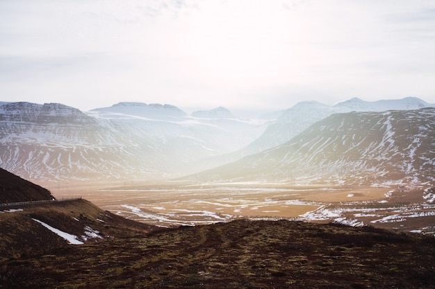 Пейзаж холмов, покрытых травой и снегом, под облачным небом и солнечным светом в исландии Бесплатные Фотографии