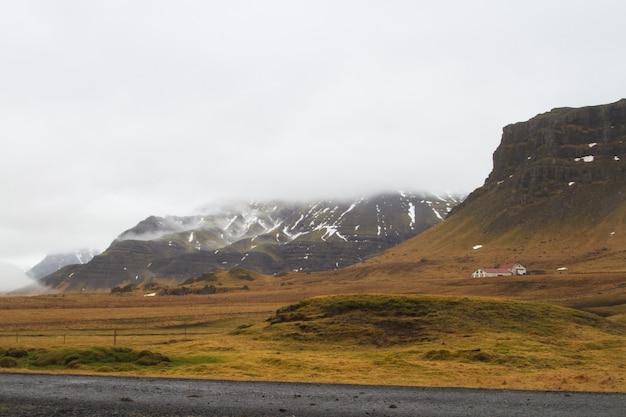 アイスランドの曇り空の下で雪と草で覆われた丘の風景 無料写真