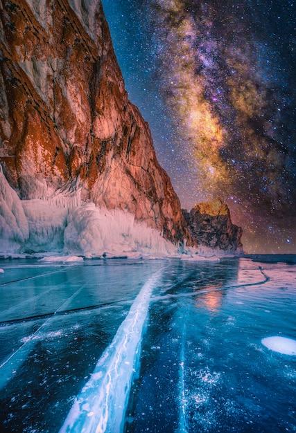 Ландшафт горы с естественным ломая льдом и млечным путем в замороженной воде на lake baikal, сибири, россии. Premium Фотографии
