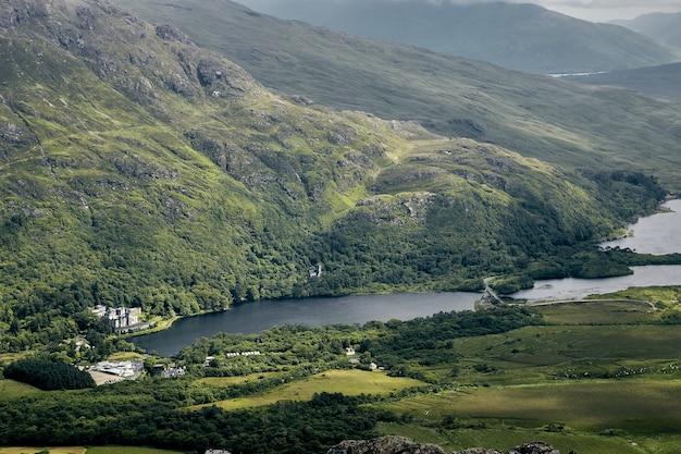 Пейзаж холмов, покрытых зеленью, под облачным небом в национальном парке коннемара, ирландия Бесплатные Фотографии