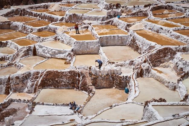 Пейзаж соляных копей марас и их рабочих в районе куско, перу, священная долина Premium Фотографии
