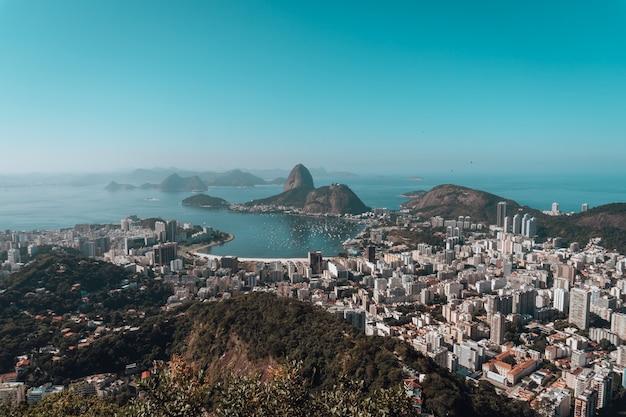Paesaggio di rio de janeiro circondato dal mare sotto un cielo blu in brasile Foto Gratuite