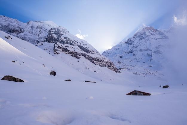 Paesaggio di montagne rocciose coperte di neve sotto un cielo nuvoloso Foto Gratuite