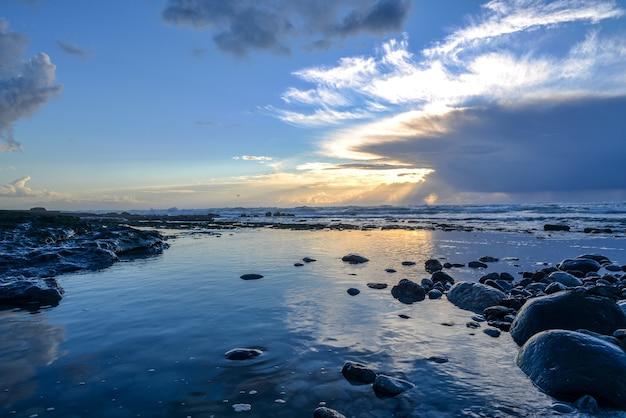 Paesaggio di un mare coperto di rocce sotto la luce del sole e un cielo nuvoloso durante il tramonto Foto Gratuite