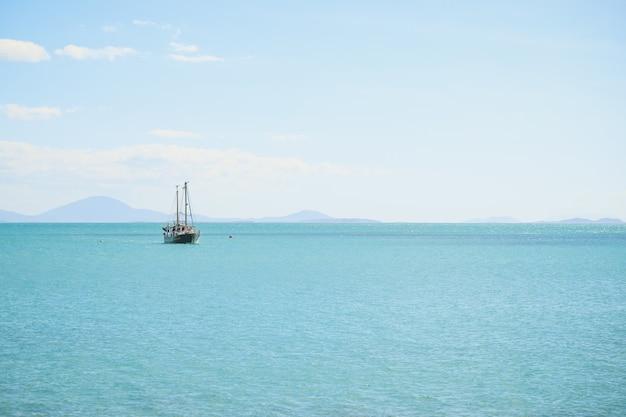 Paesaggio del mare con una nave su di esso sotto un cielo blu e luce solare Foto Gratuite